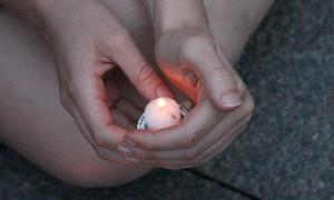 Photograph of hands cradling a candle